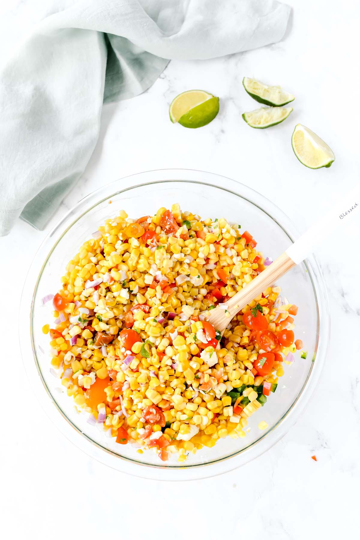 Corn salad with feta and lime wedges on a white table.