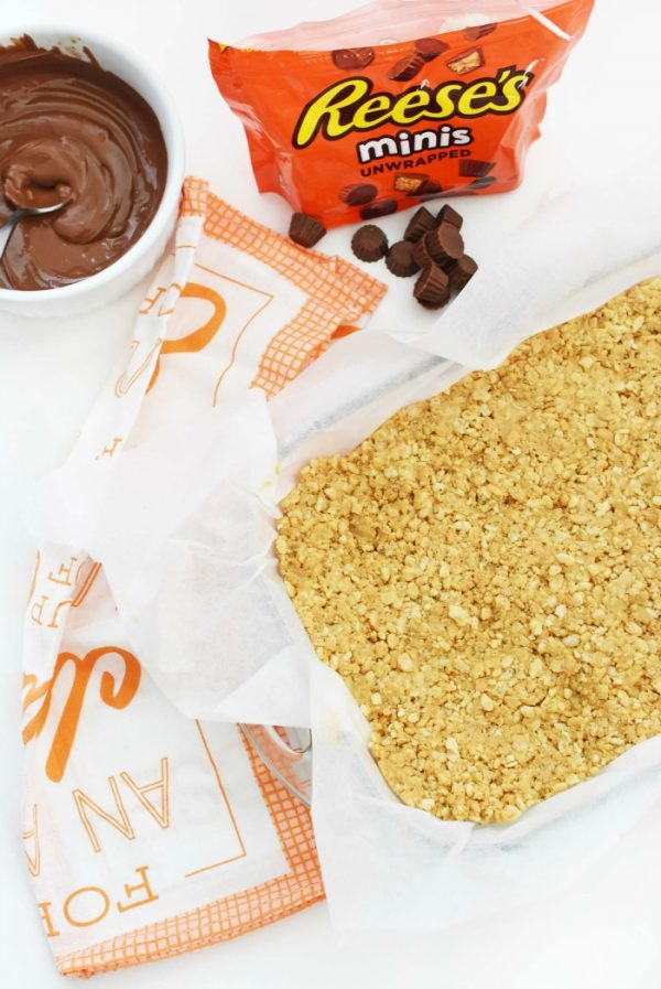 Peanut Butter Rice Cereal Bars base inside a pan lined with parchment paper on a table with reese's minis candy.