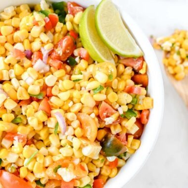 Zesty Corn salad in a white bowl with green lime wedges.