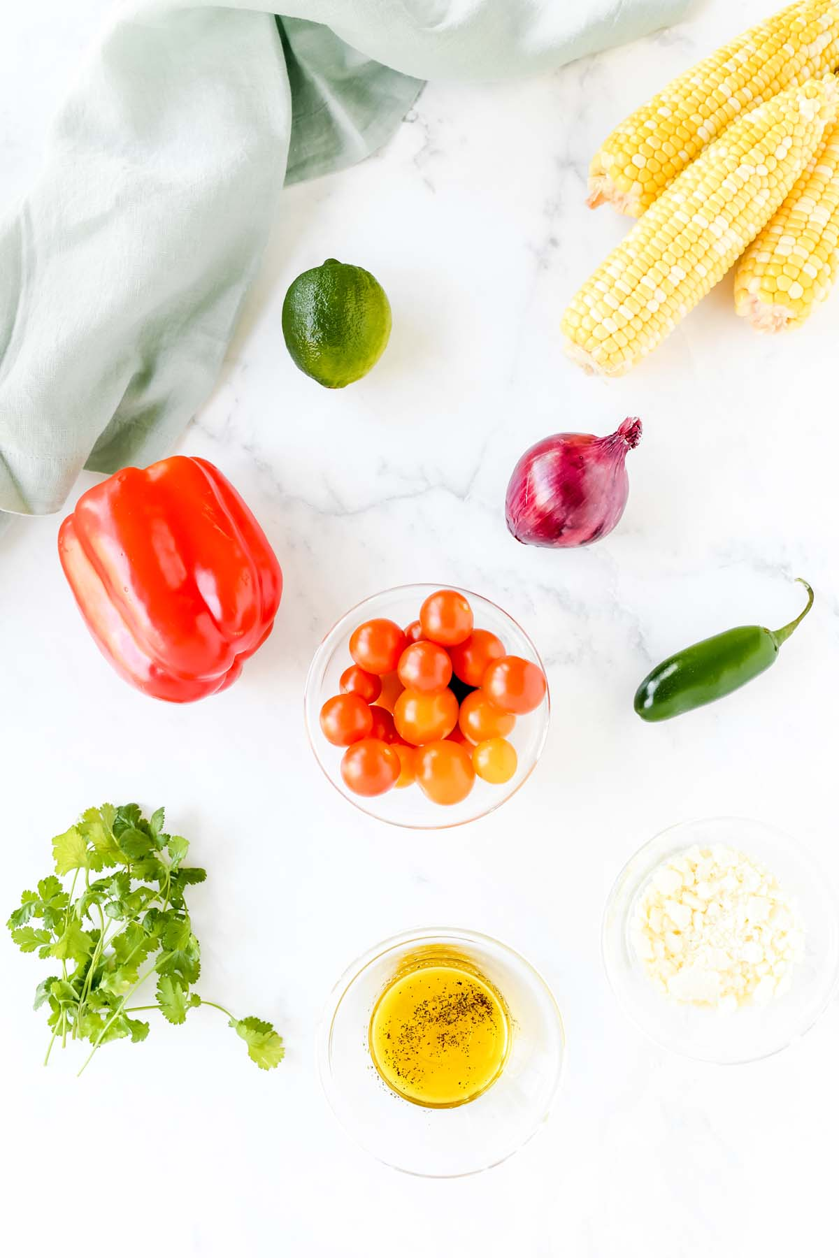 peppers, corn, lime, cilantro, onion, and oil on a white table.