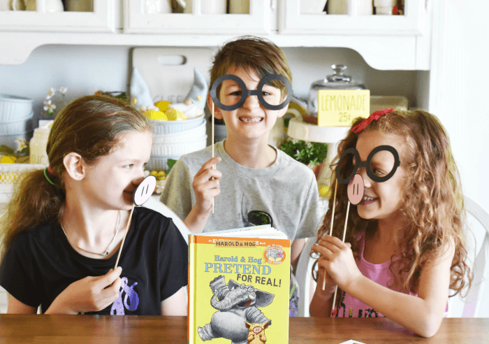 kids with Piggie and Gerald book and props in kitchen