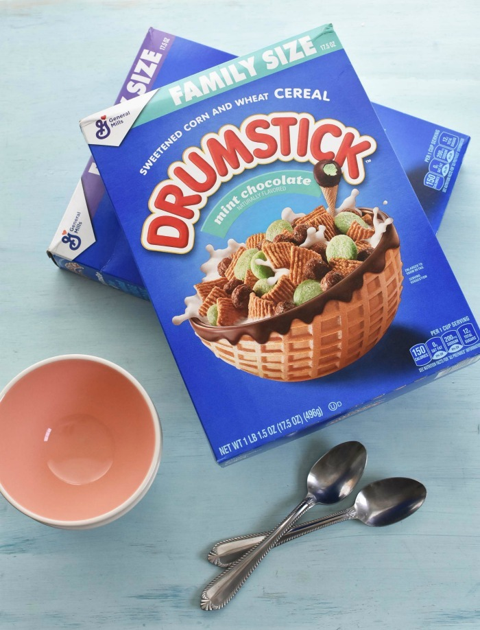 Family Size Drumstick Cereal boxes on blue table with bowls