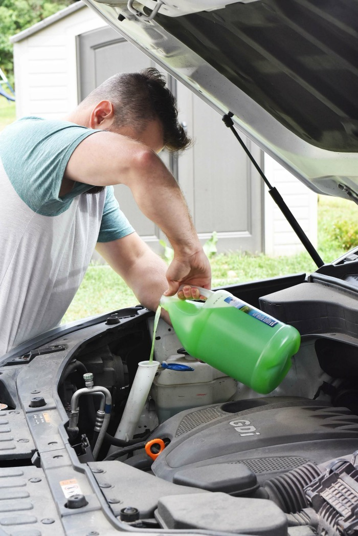Man adding windshield washer fluid