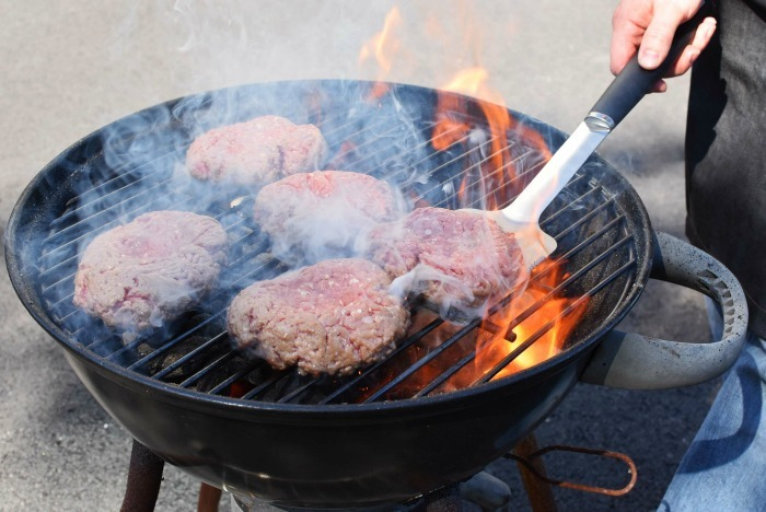 Burgers on grill with flames being turned with a spatula.