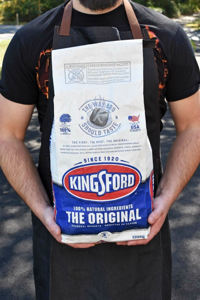 Man holding a Kingsford Charcoal Bag.