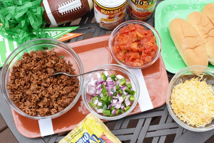 Taco Hot Dog toppings on patio table.