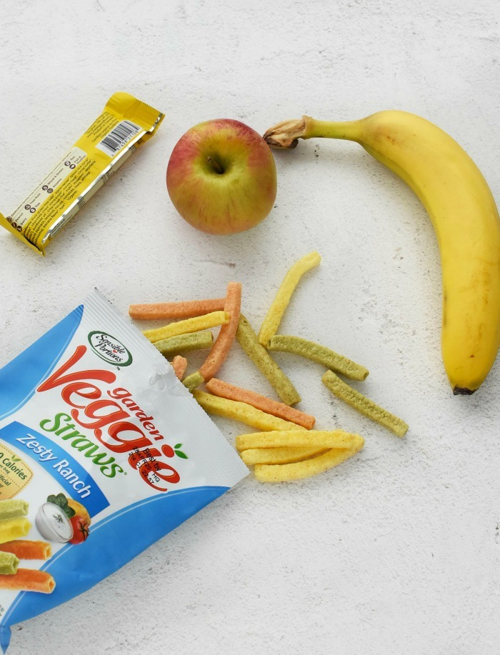 Veggie straws snacks on grey table with fresh fruit.