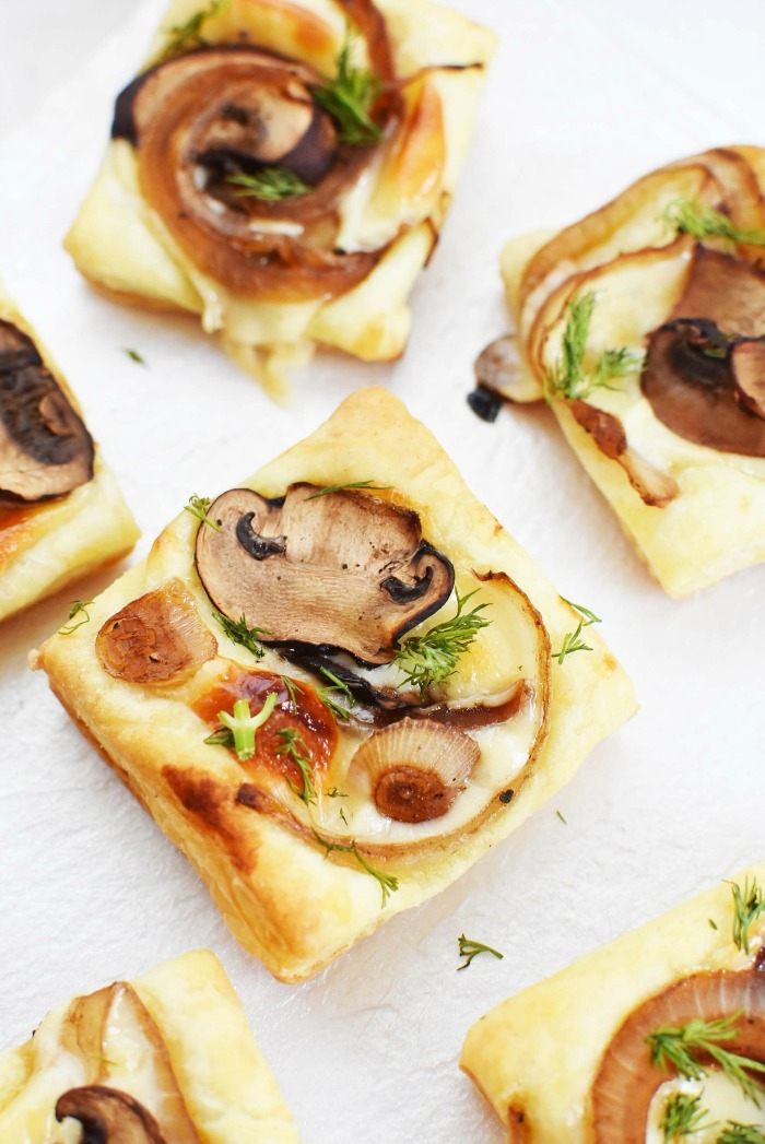 Mushroom and onion baked puff pastry appetizers on a white serving dish.