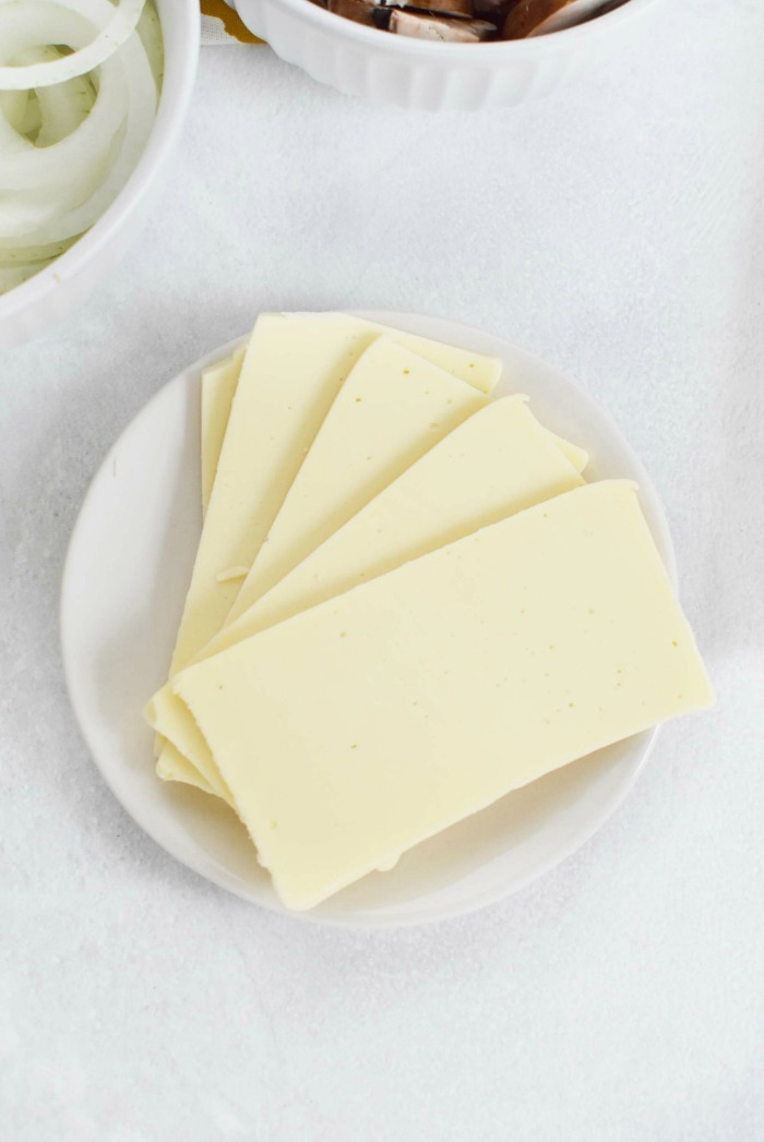 Cooper Sharp White Cheese sliced on white plate.