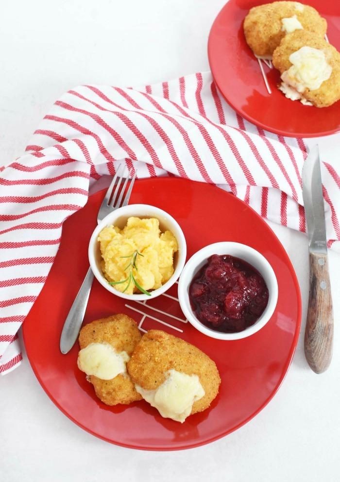 Easy chicken dinner with potatoes and cranberry sauce on a red plate with a striped napkin.