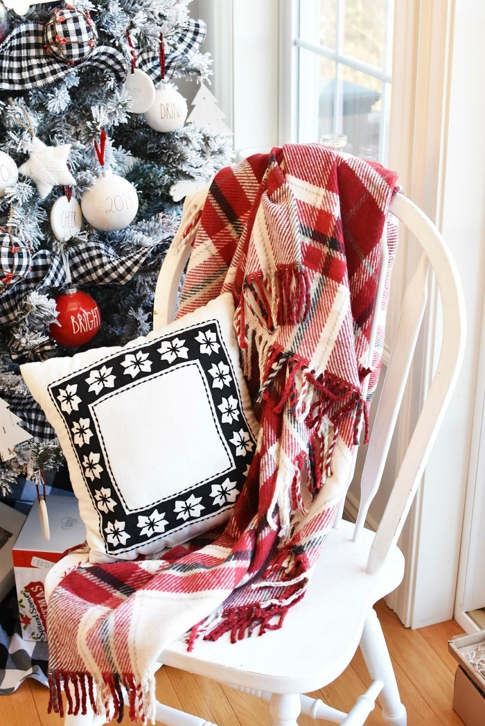 Farmhouse Styled Chair with black and white pillow and red plaid throw.