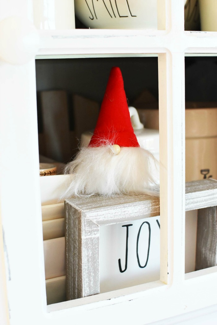 Gnome with red hat in cabinet.
