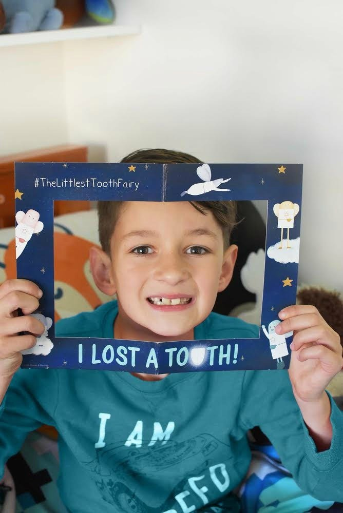 Boy smiling with Littlest tooth Fairy sign.