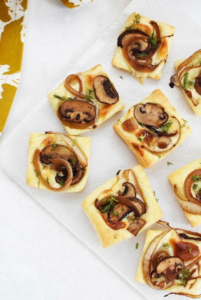 Puff Pastry Mushroom Onion Cheese Bites on white serving platter.