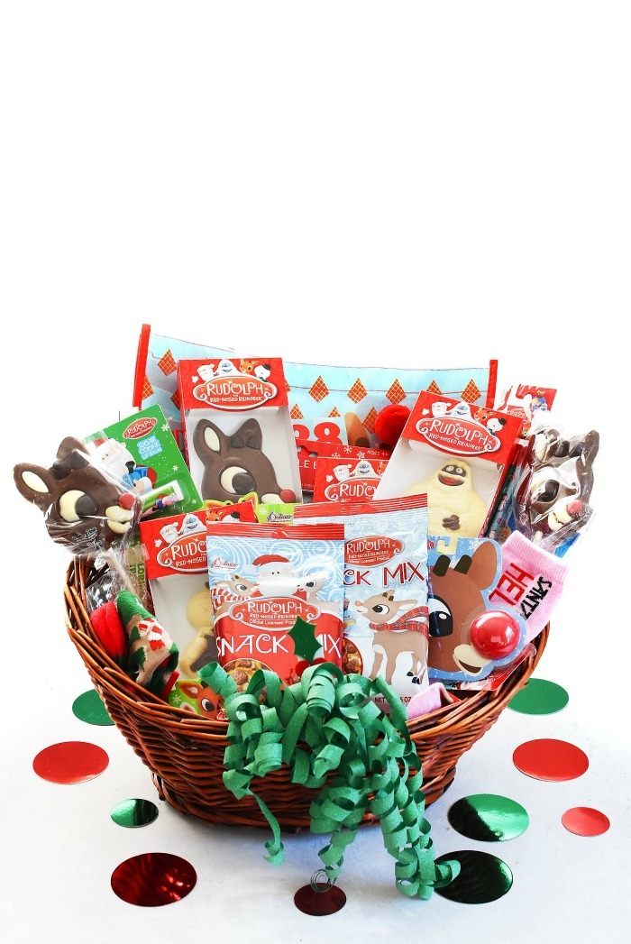 Reindeer Gift basket filled with Christmas candy and toys on white table.