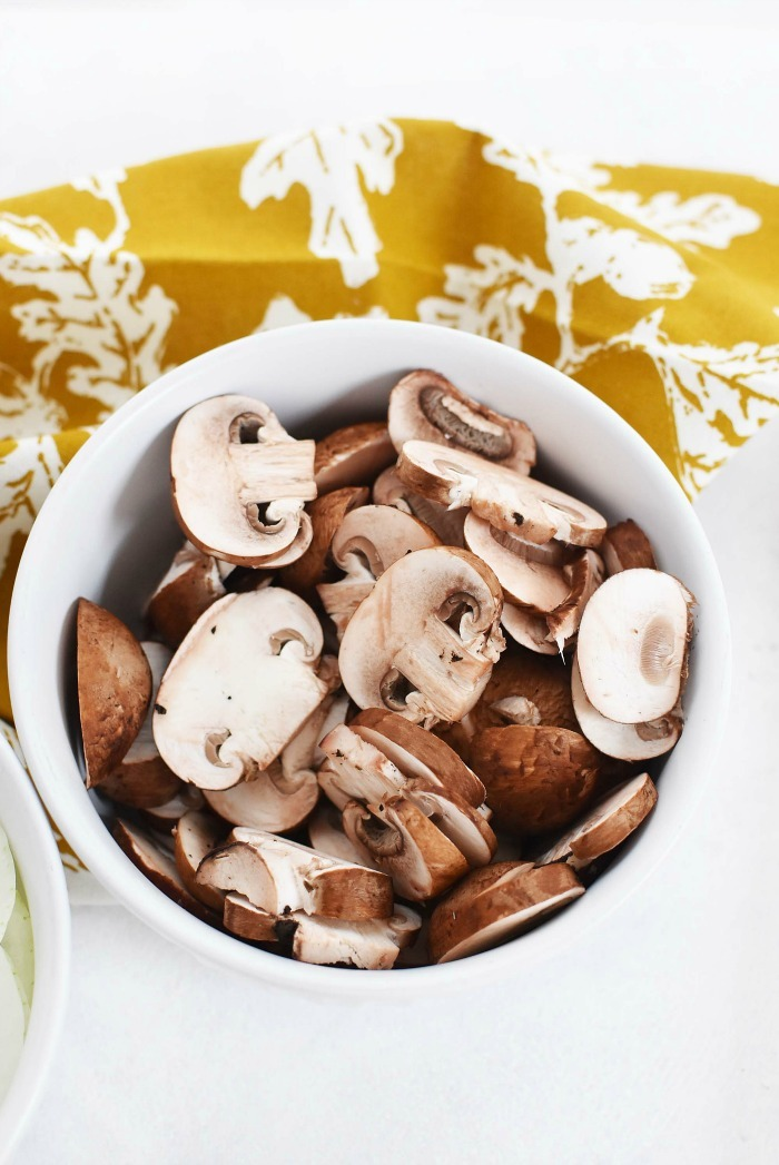 Sliced Mushrooms in a white bowl.