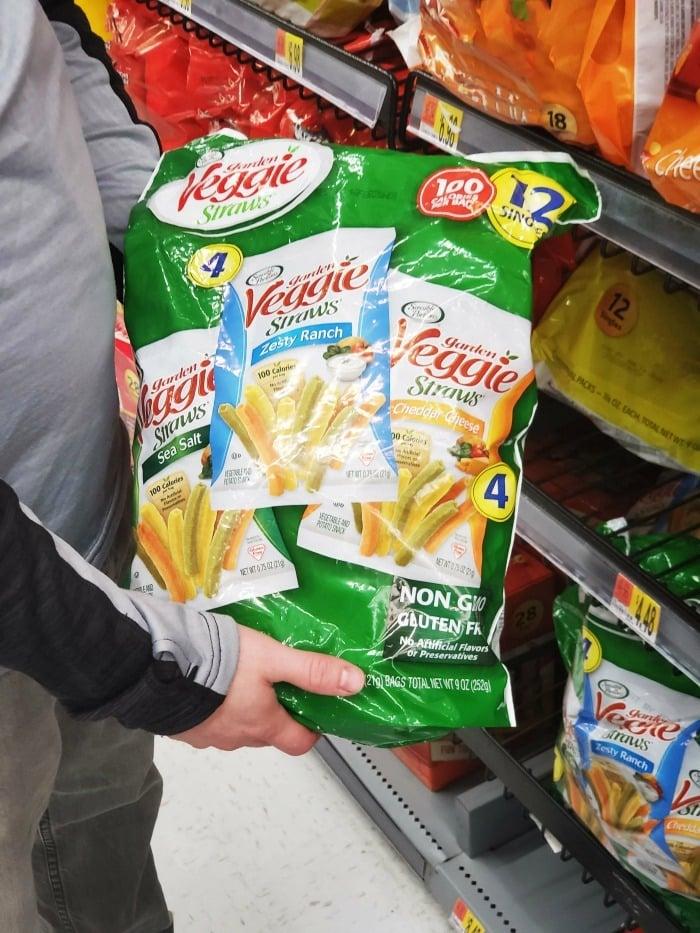 Man holding Veggie straws at Walmart in aisle.