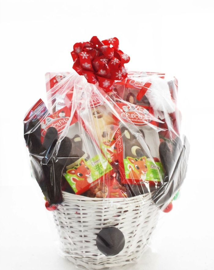 Wrapped Reindeer Gift basket with antlers on white table.