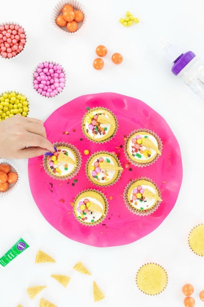 Hand grabbing cornucopia cupcakes on a pink tray.