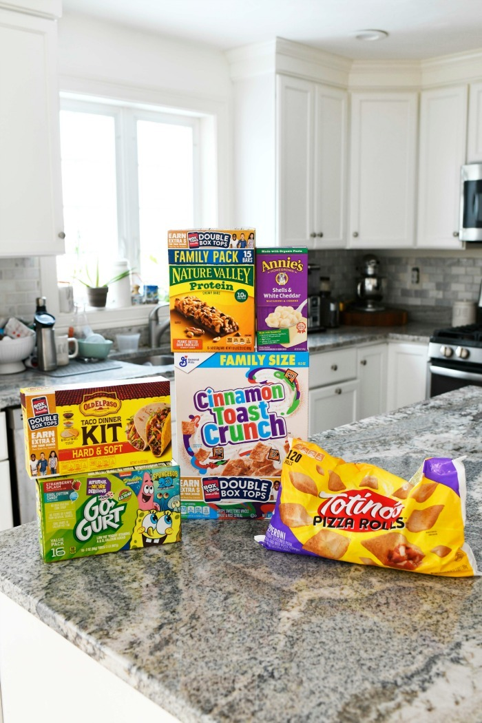 Box Tops groceries on granite counter in white kitchen.