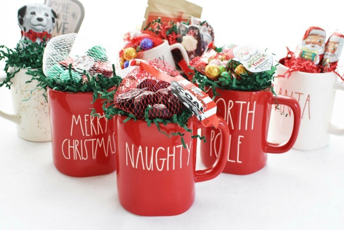 Rae Dunn Christmas mugs filled with candy.