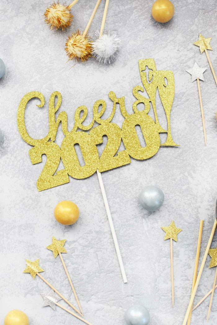 Cheers 2020 cake topper on grey table.
