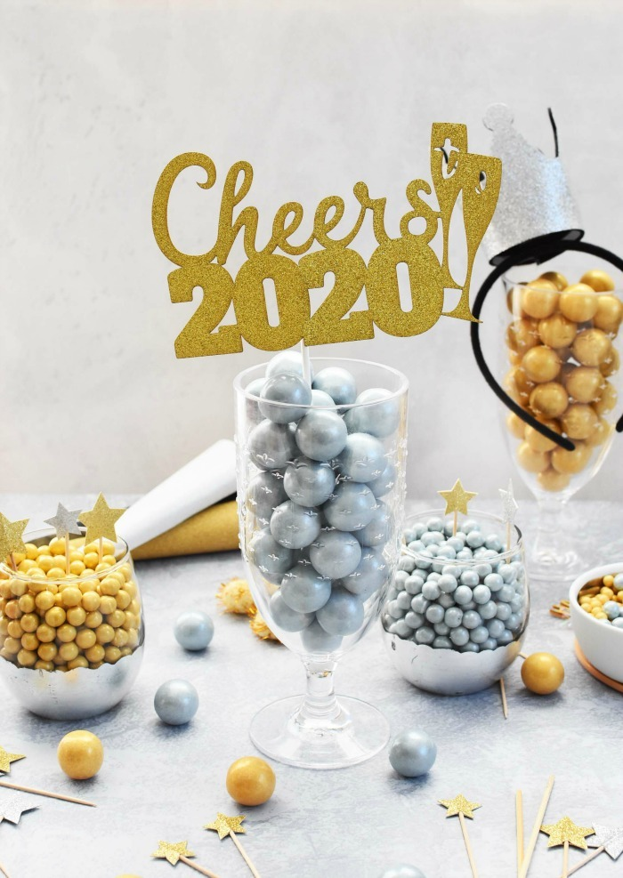 Cheers to 2020 gold, glittery sign and gold and silver candies.