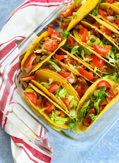 Chicken Taco Bake with red striped napkin in a glass casserole dish