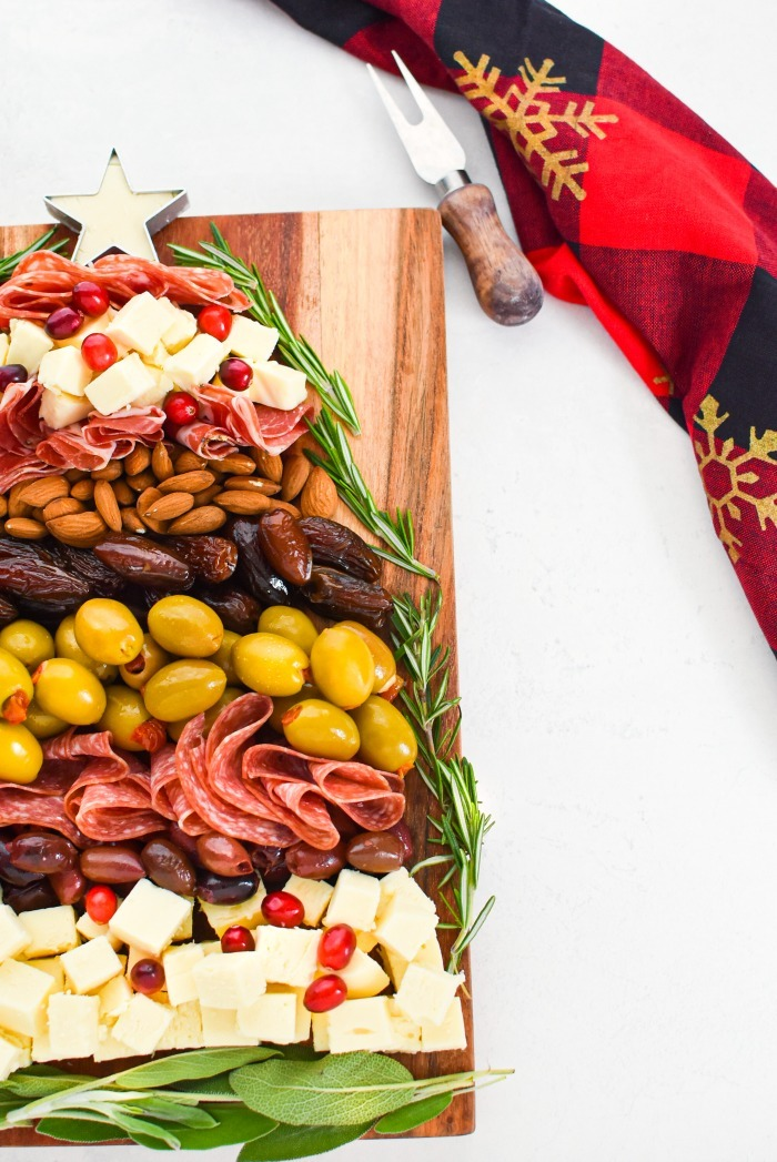 Christmas Tree Cheese, Olives, Meat Board side view with red, plaid napkin.