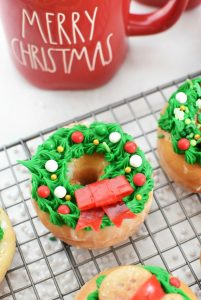 Wreath donut on baking sheet with red candy bow