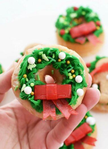 Christmas Wreath Doughnut held by a hand.