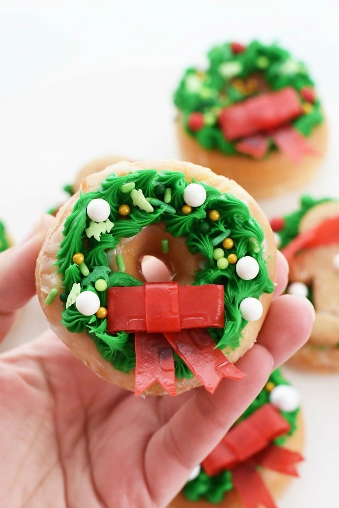 Christmas Wreath Doughnut with red bow in hand.