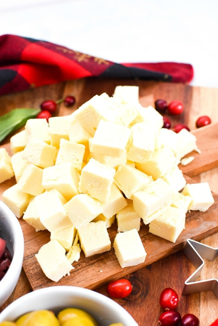 Cooper Cheese Cubes on wooden cutting board.