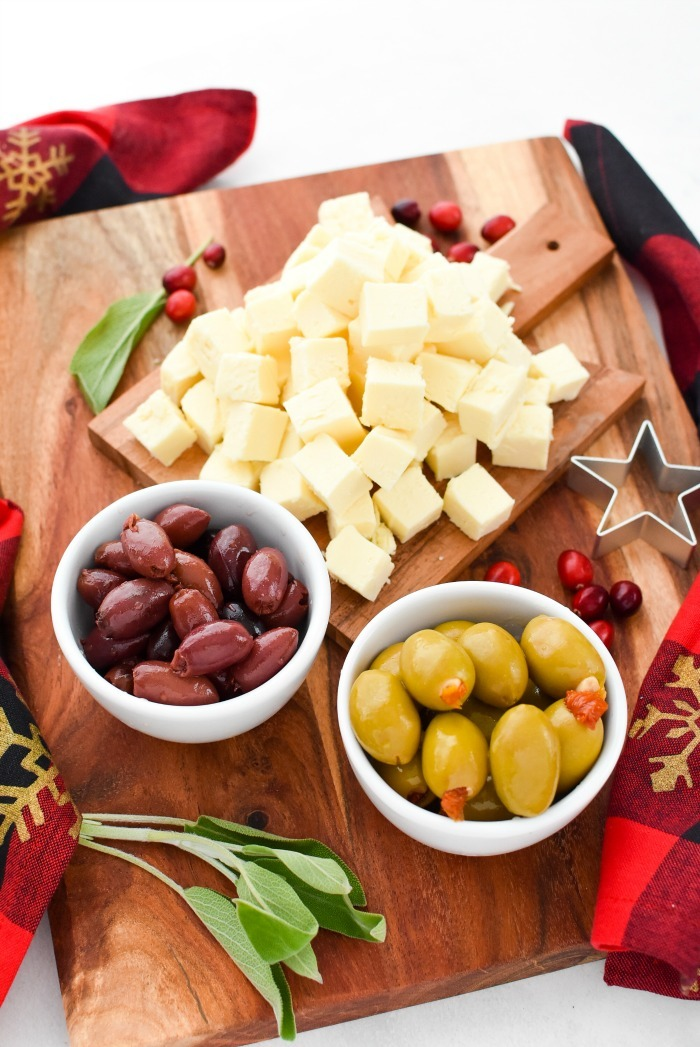 Cooper Cheese and Olives on wooden cutting board.