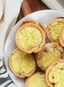 Custard Tarts in a white plate with a tan napkin, on a wood table.