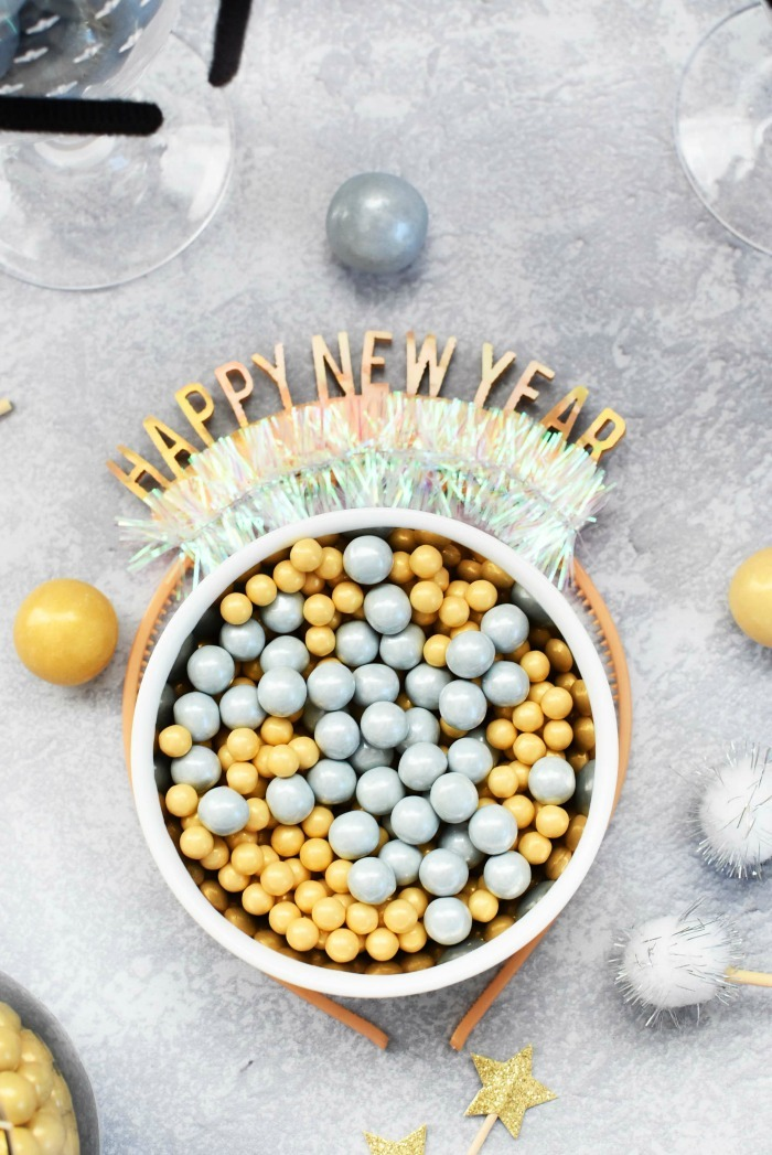 Gold and Silver candies in a dish with Happy New Year.