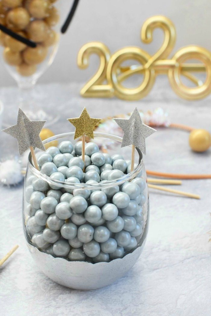 Silver Sixlets in a glass with glittery star picks.
