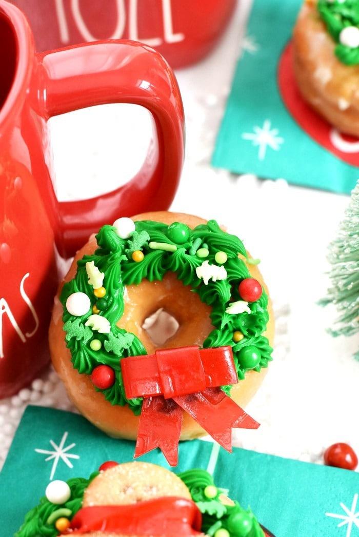 Wreath Christmas Donut near a red Christmas mug on a table.