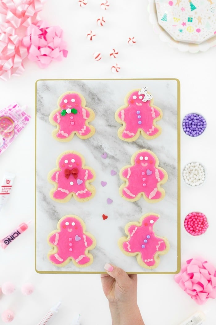 Pink Gingerbread men on a granite board in someone's hand.