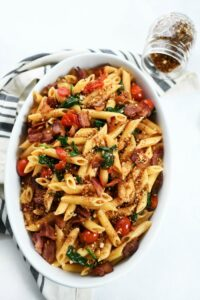 BLT Pasta in white oval dish with a striped towel