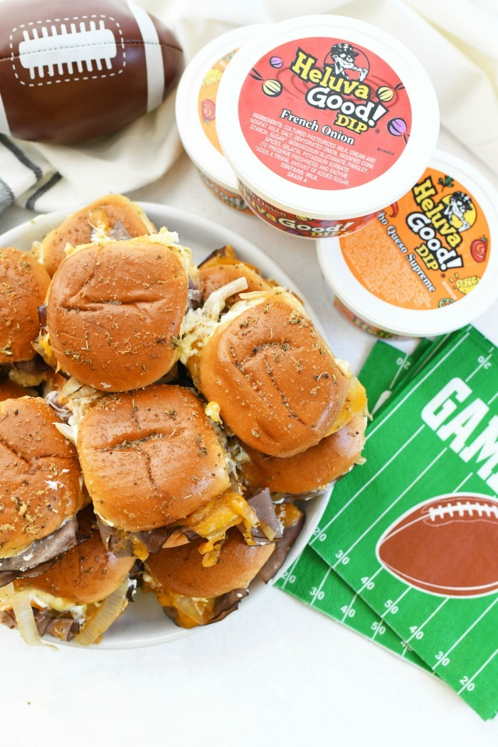 Baked Roast Beef Sliders on platter near game day napkins and dip.