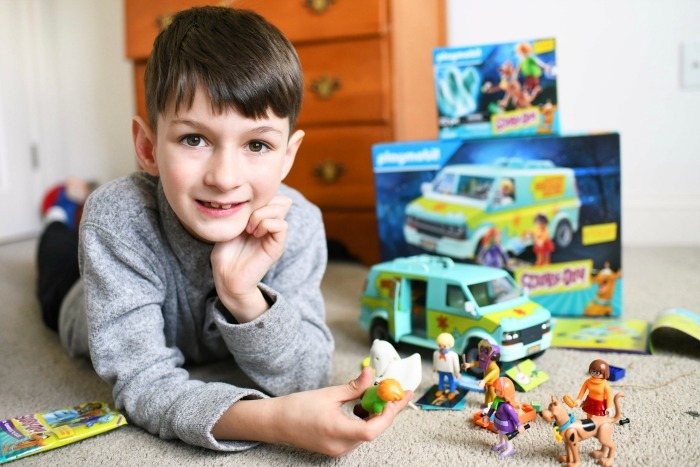 Boy playing with Scooby Doo Playmobil toys