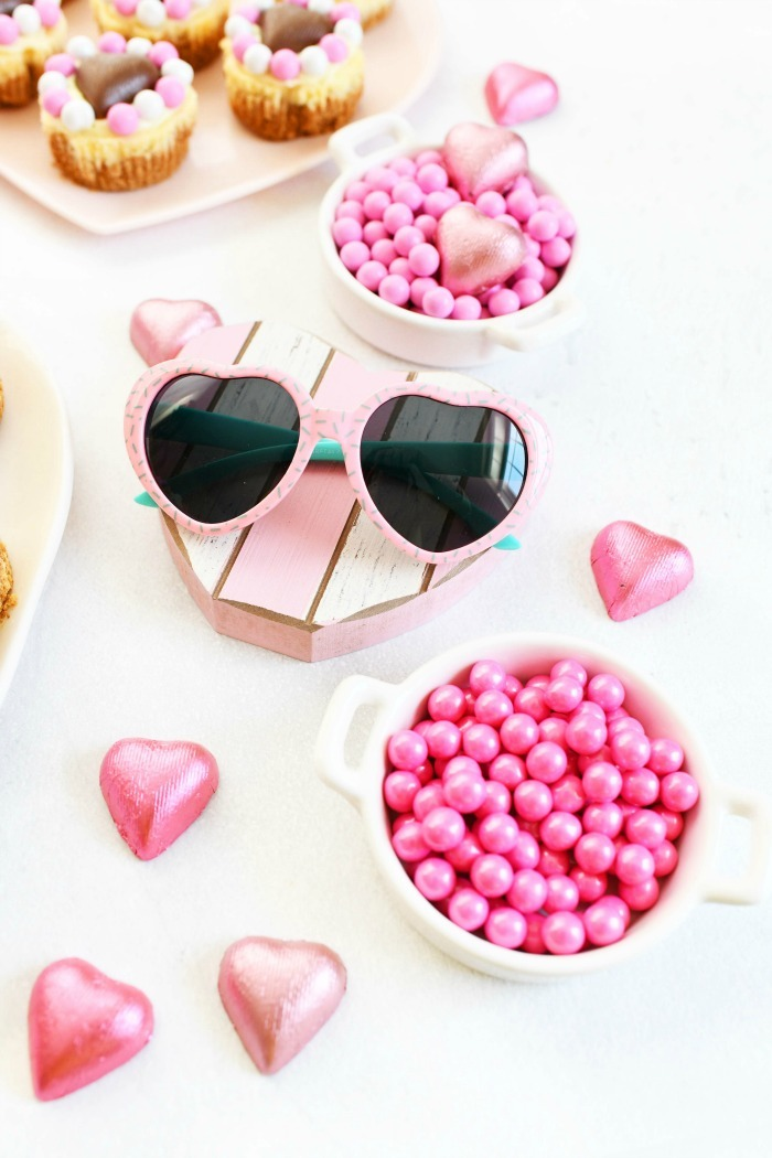 Bright Pink Sixlets with sunglasses on a table.