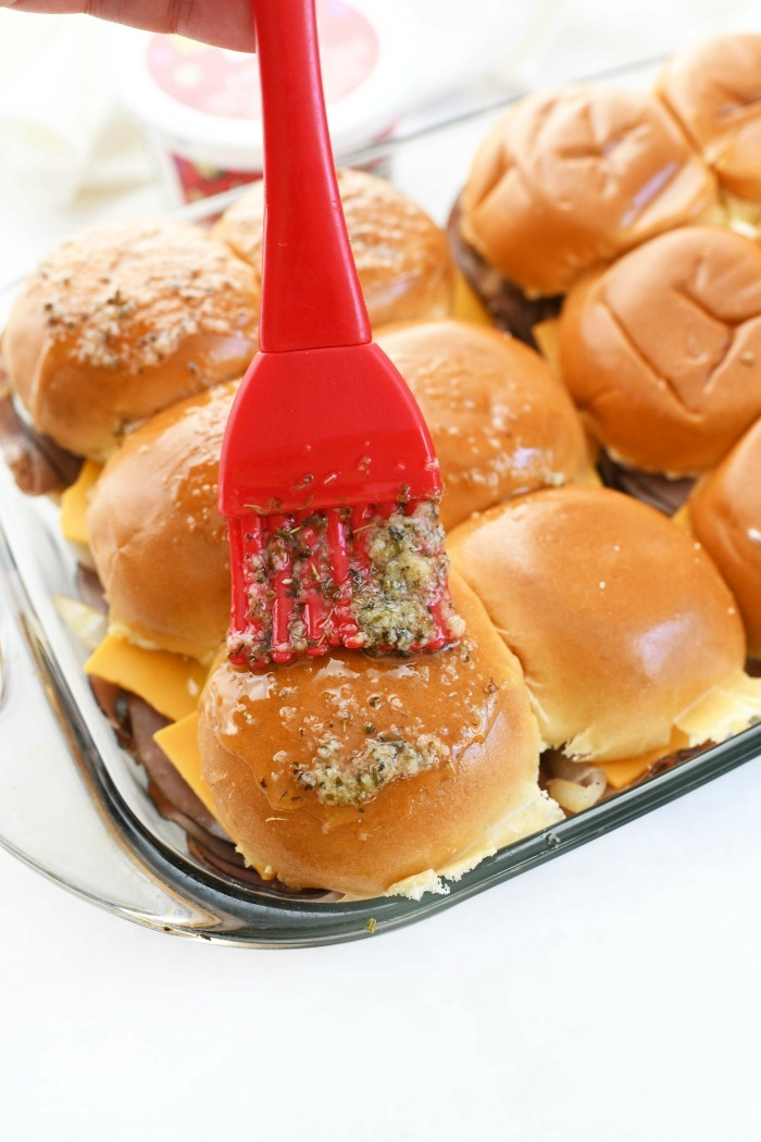 Garlic Butter brushed sliders with red, rubber brush.