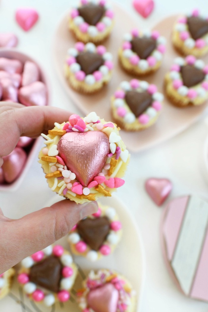Heart Cheesecake in hand with pink foiled candy.