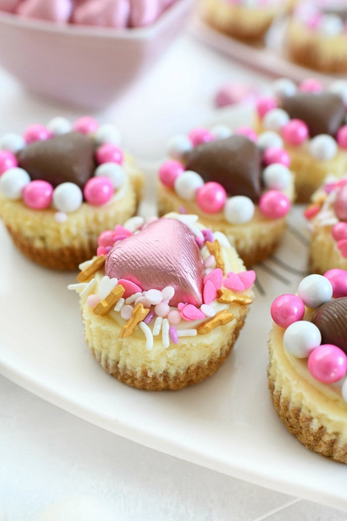 Heart cheesecakes with pink candy hearts and sprinkles.