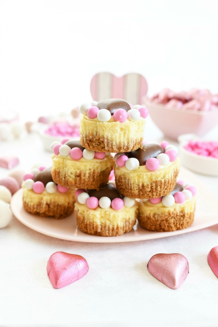Mini Valentine's Cheesecakes stacked up close on a pink heart plate.