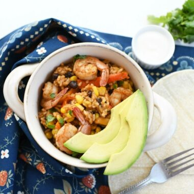 One-Pot Mexican Shrimp in a white handled bowl with fresh sliced avocado.