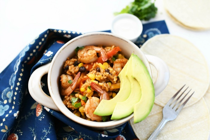 One-Pot Mexican Shrimp Rice and Beans in white bowl with avocado slices.