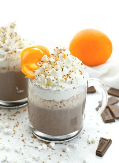 Orange Hot Chocolate Recipe on a white table with orange and zest